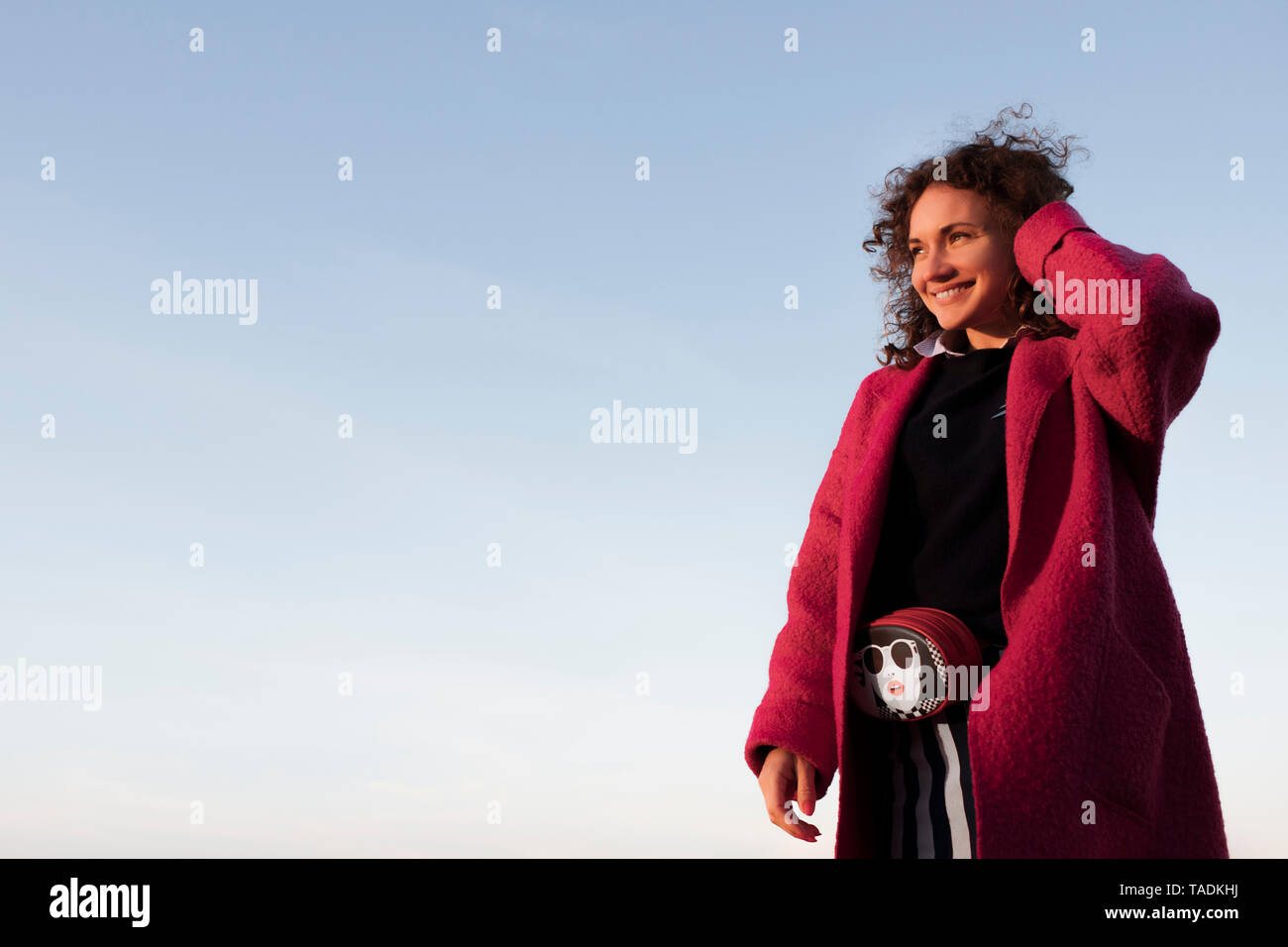 Portrait of smiling woman with curly hair - Stock Image