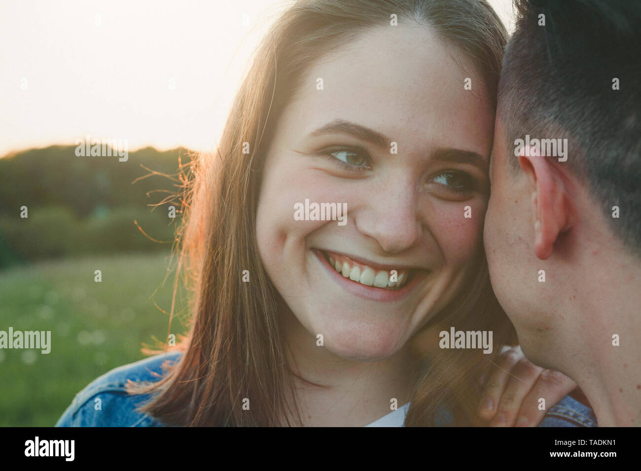 Portrait of teenage girl in love close to her boyfriend by sunset - Stock Image