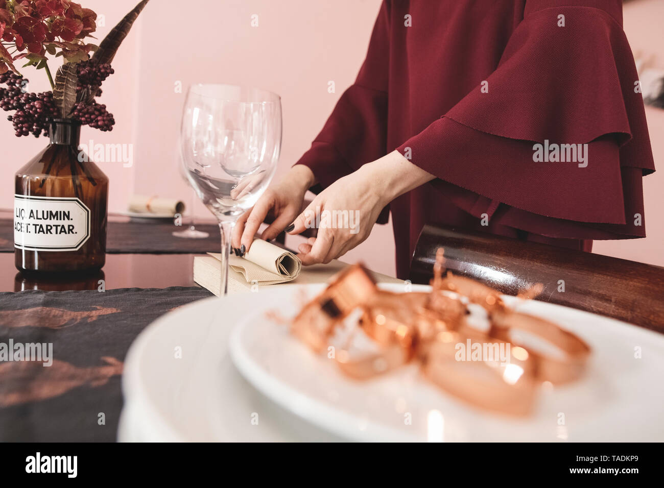 Close-up of elegant woman laying the table - Stock Image