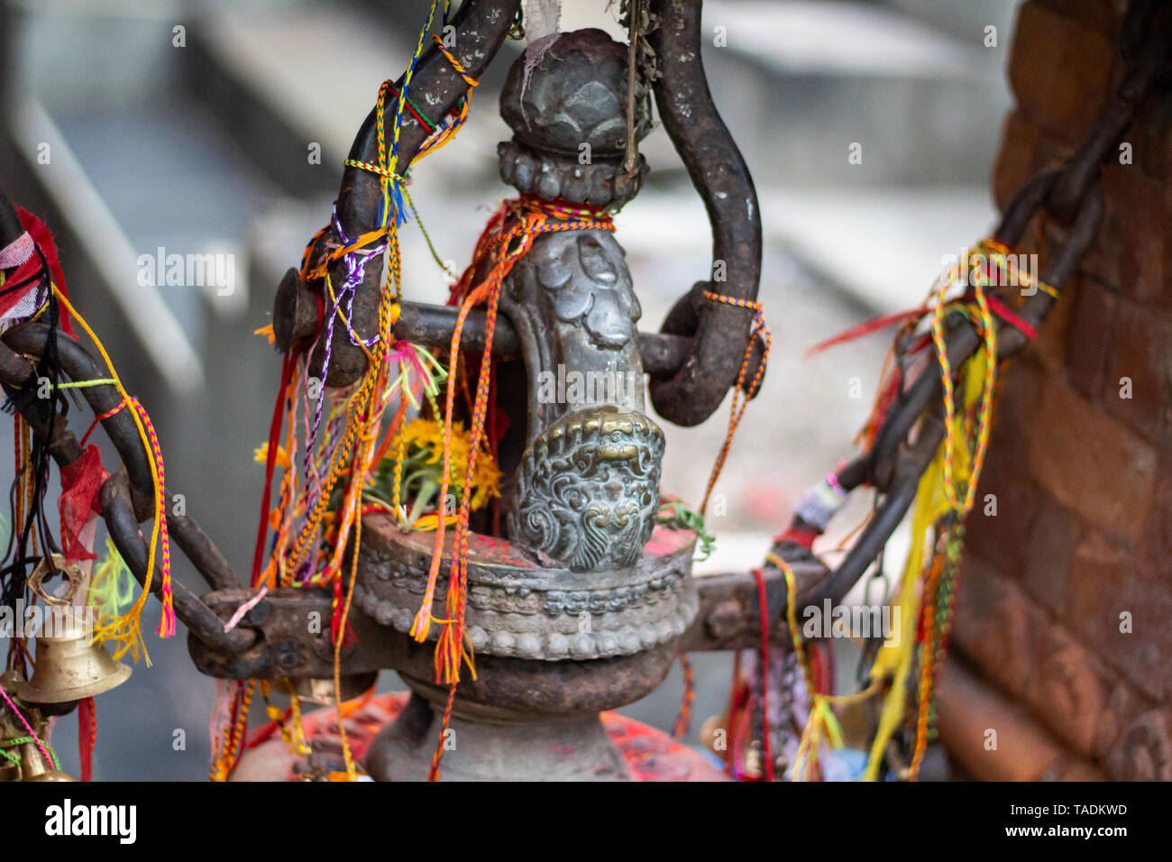 Sacred thread tied around bronze statue in Pokhara lake temple in Nepal. - Stock Image