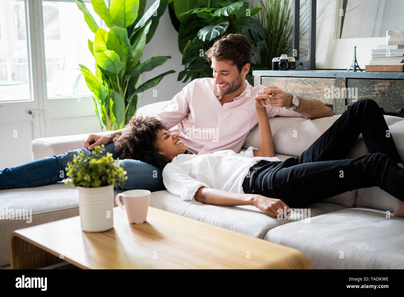 Affectionate couple relaxing on sofa - Stock Image