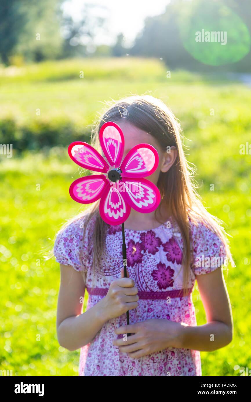 Girl hiding her face behind pinwheel - Stock Image