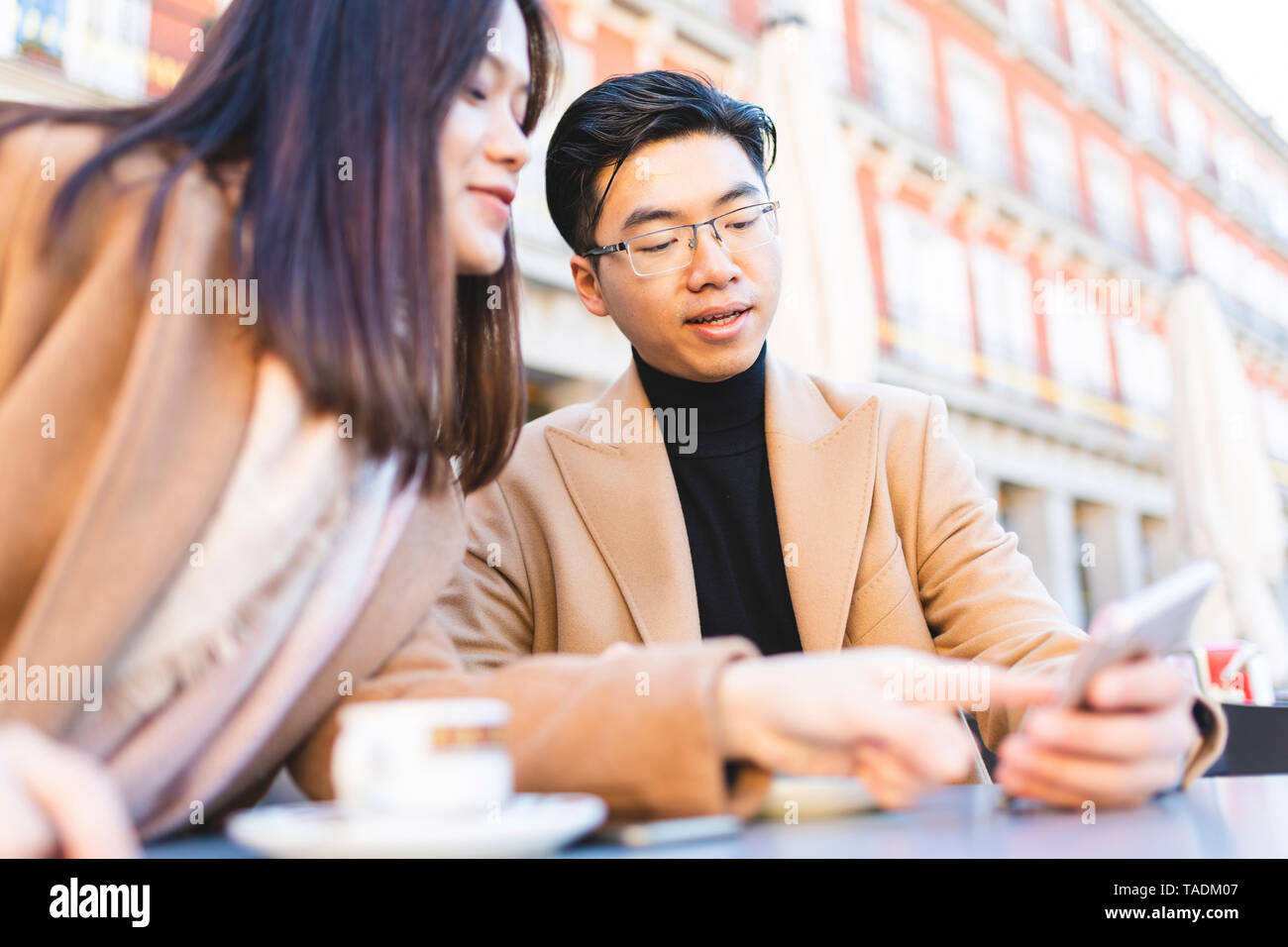Spain, Madrid, young couple using cell phone in a cafe at Plaza Mayor - Stock Image