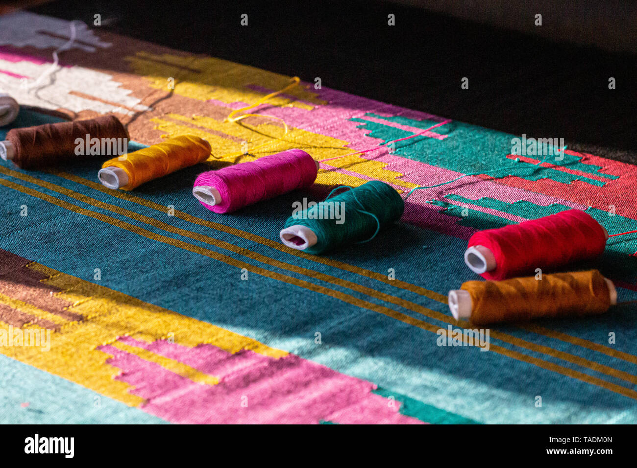 Pokhara traditional loom weaving in yellow, pink and green. - Stock Image