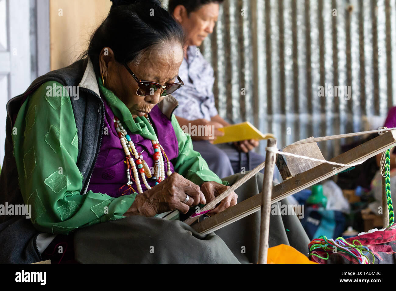 Tibetan exiled woman in refugee camp living in Nepal making a living of weaving on a loom. - Stock Image