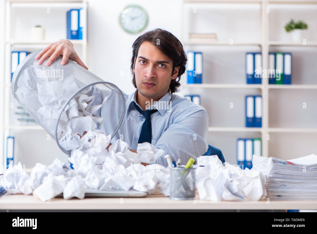 Businessman rejecting new ideas with lots of papers - Stock Image