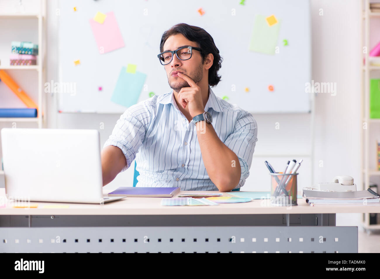 Young handsome male designer working in the office - Stock Image