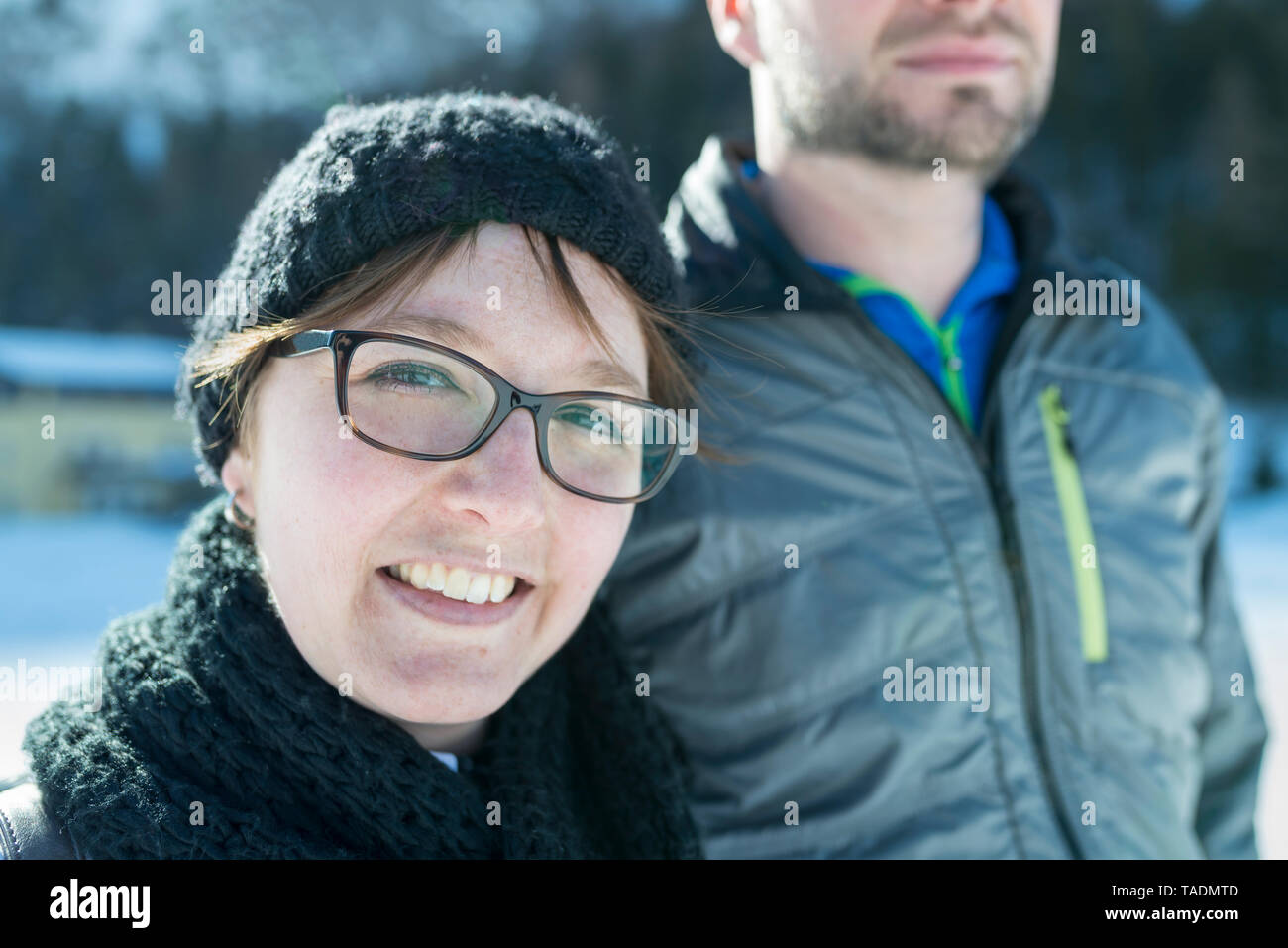 Portrait of smiling woman with man outdoors in winter - Stock Image