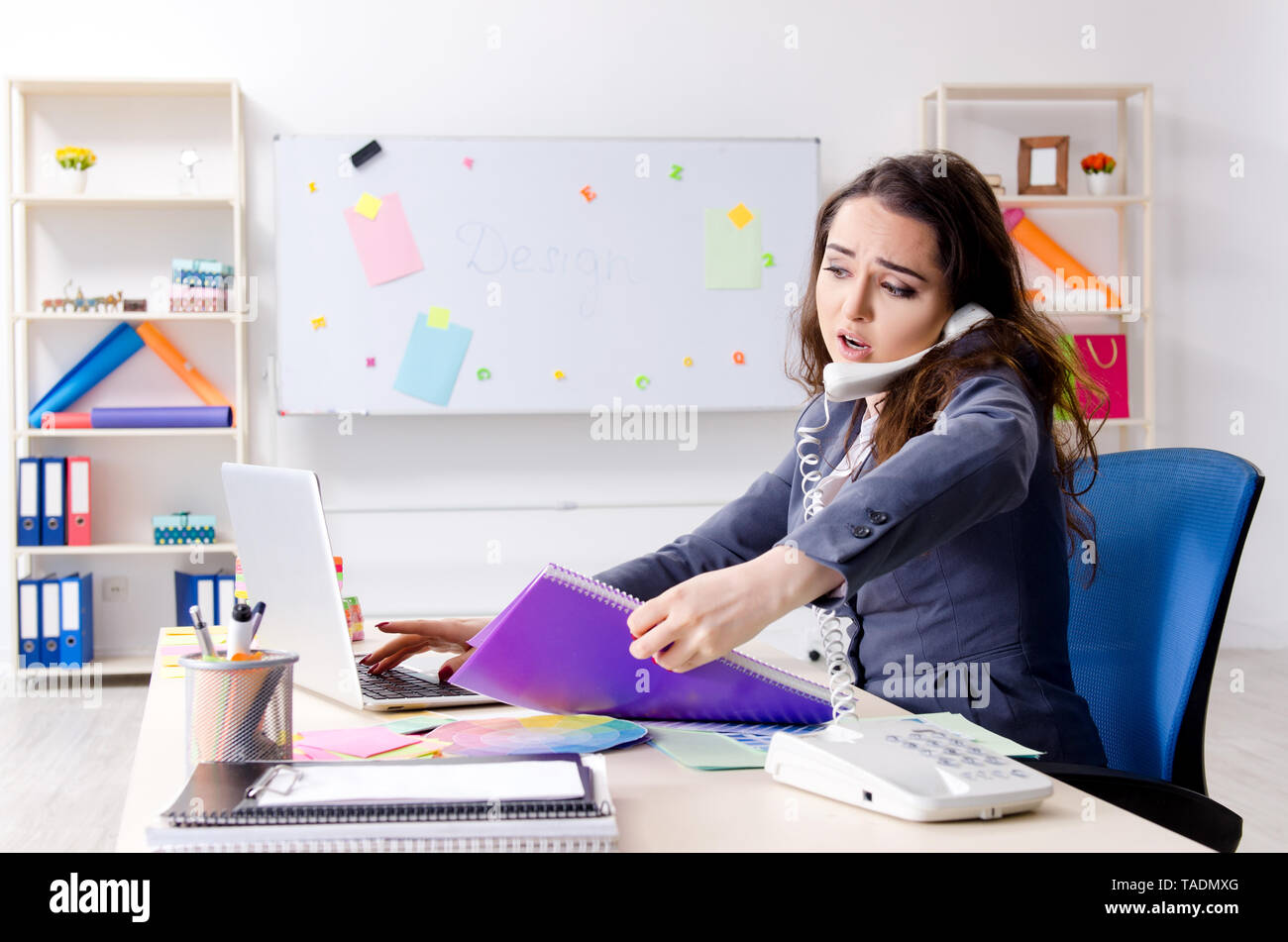 Young female designer working in the office - Stock Image