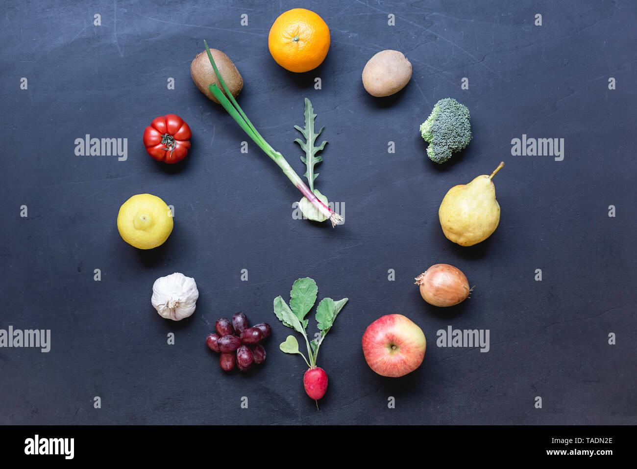 Fruits and vegetables buliding clock on dark ground - Stock Image