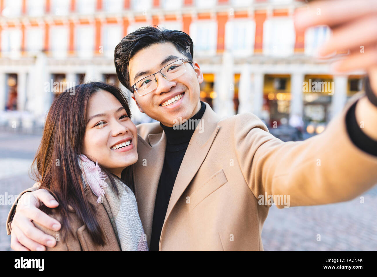 Spain, Madrid, happy young couple taking a selfie in the city - Stock Image