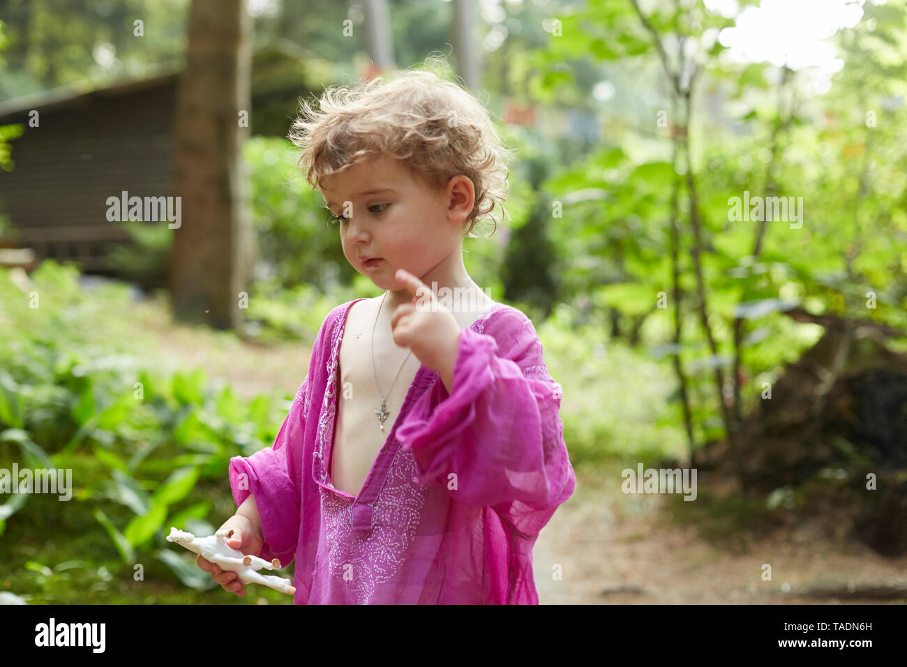 Little girl wearing pink tunic in nature holding horse figurine - Stock Image