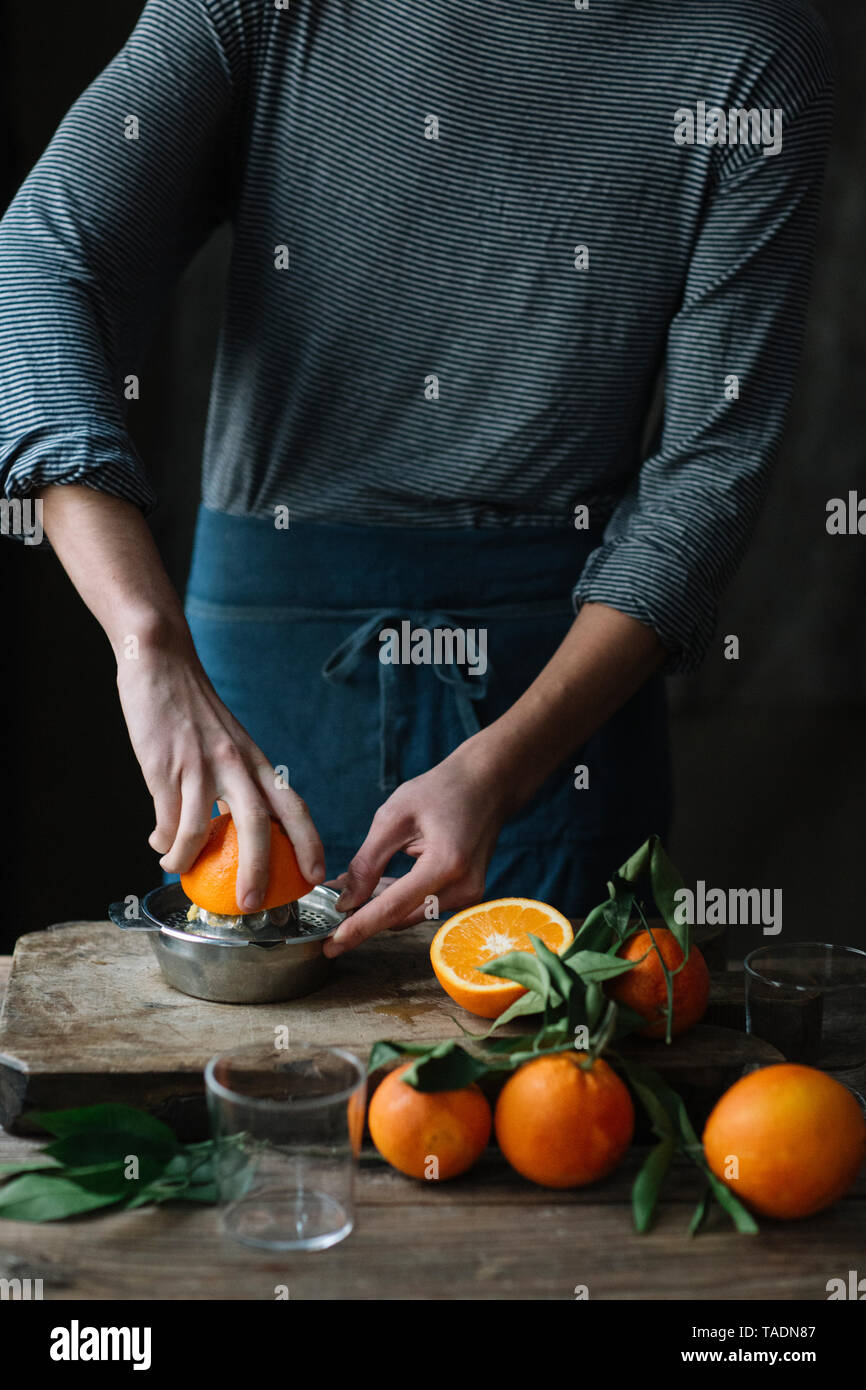 Young man squeezing orange, partial view - Stock Image