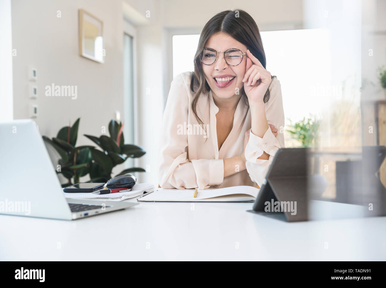 Portrait of happy young woman sitting at table at home twinkling - Stock Image