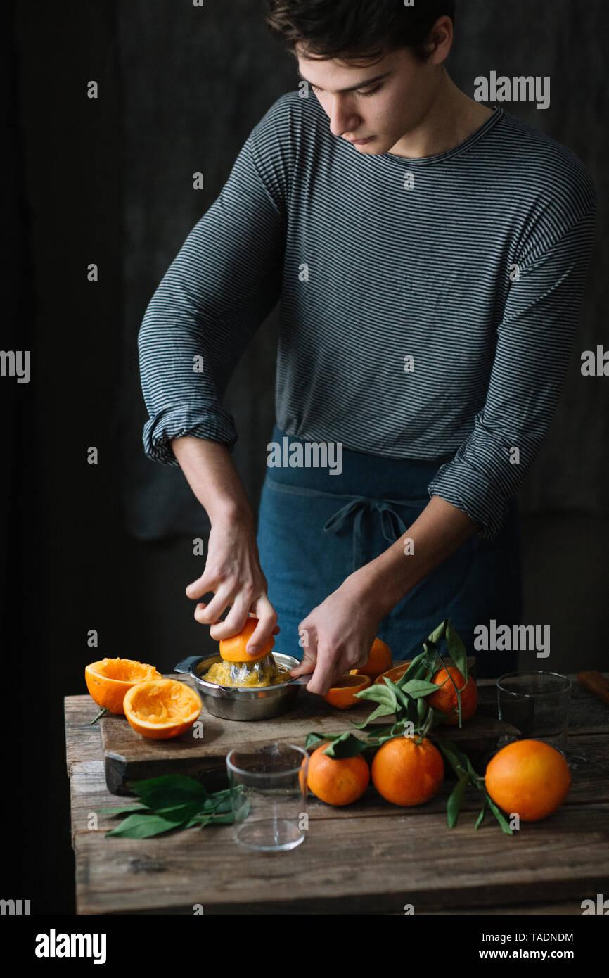 Young man squeezing orange - Stock Image