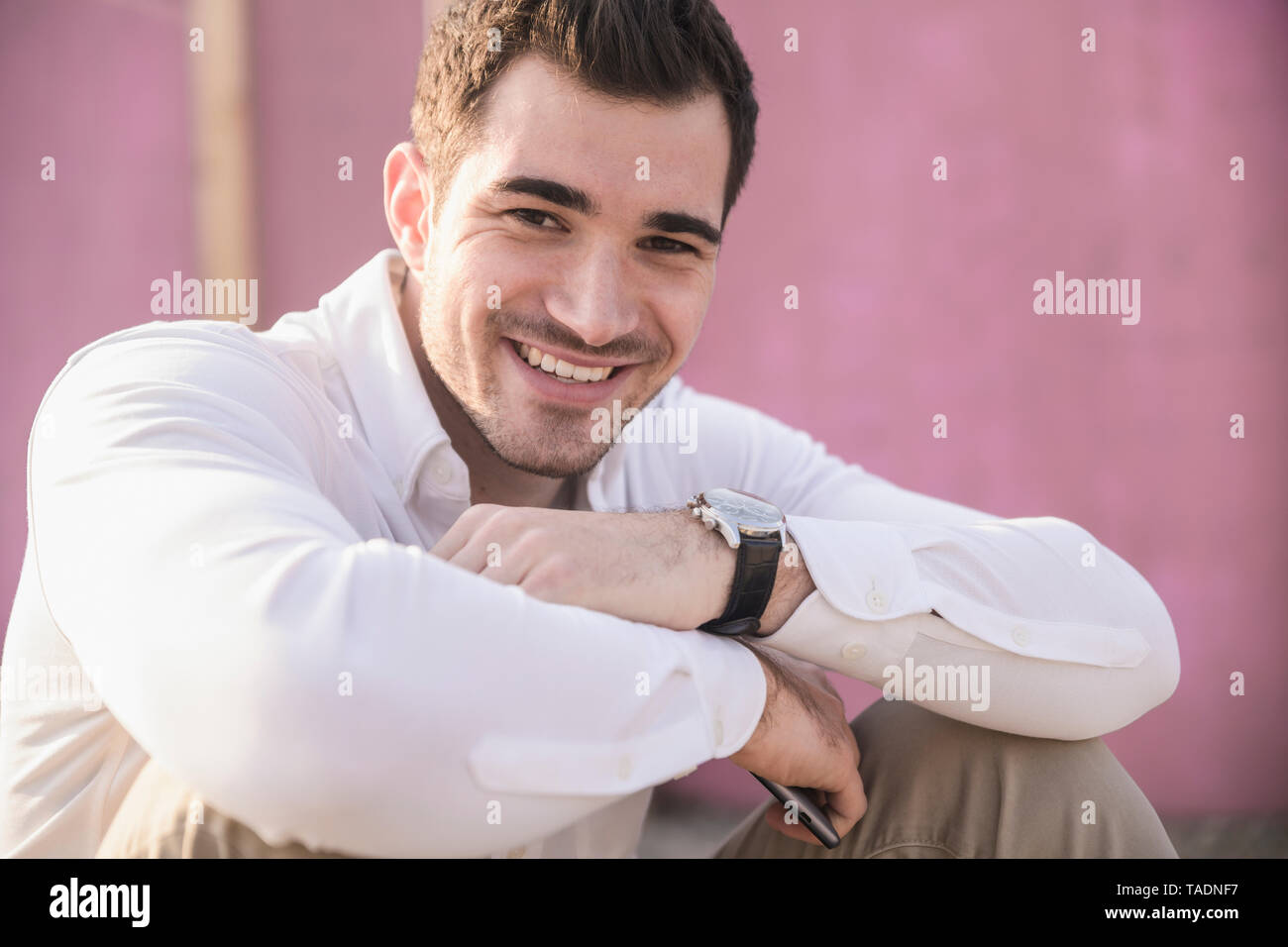 Portrait of smiling young man in front of pink wall - Stock Image