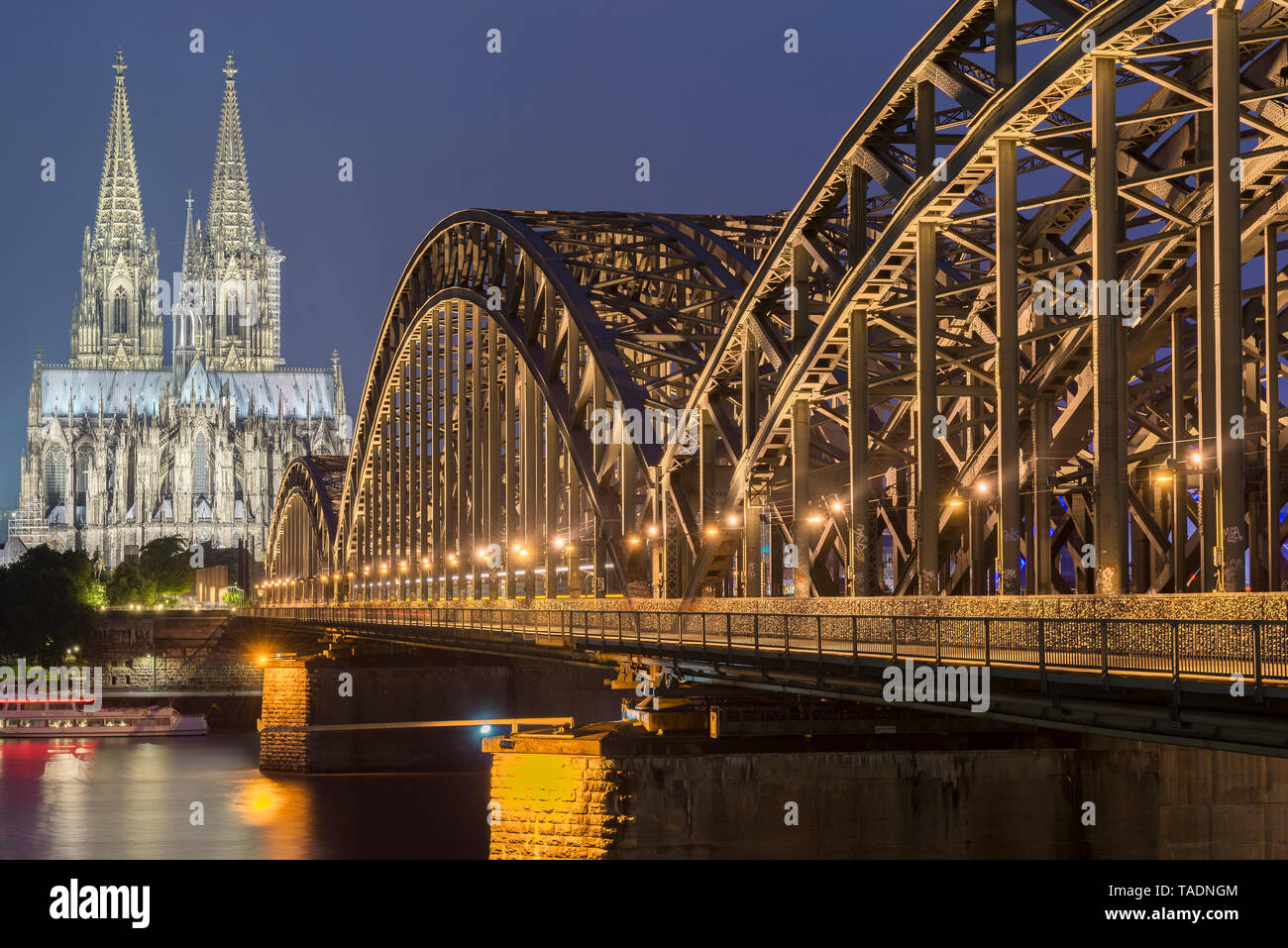 Germany, Cologne, view to lighted Cologne Cathedral with Hohenzollern Bridge in the foreground - Stock Image