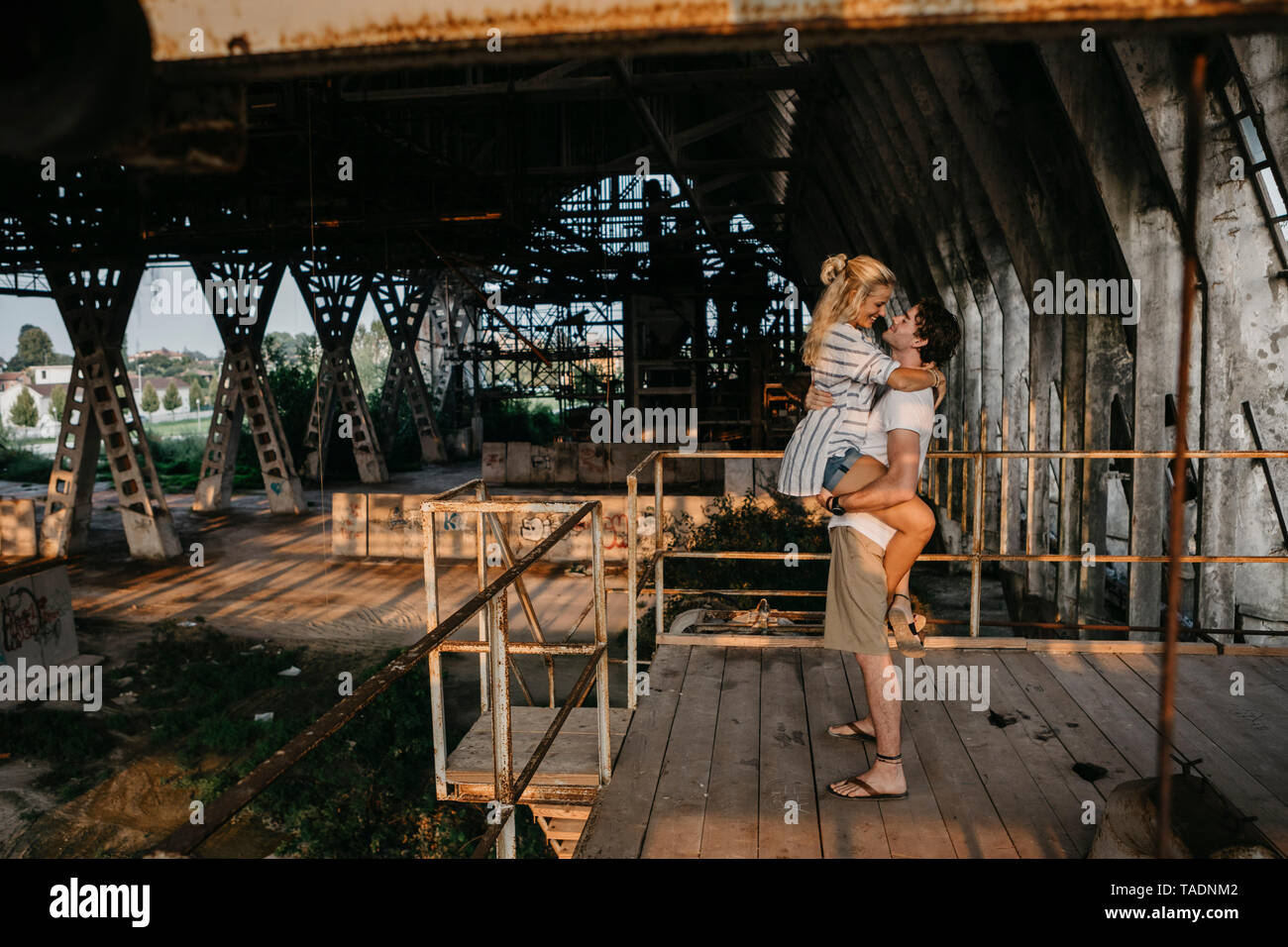 Happy young man carrying girlfriend in an old train station - Stock Image