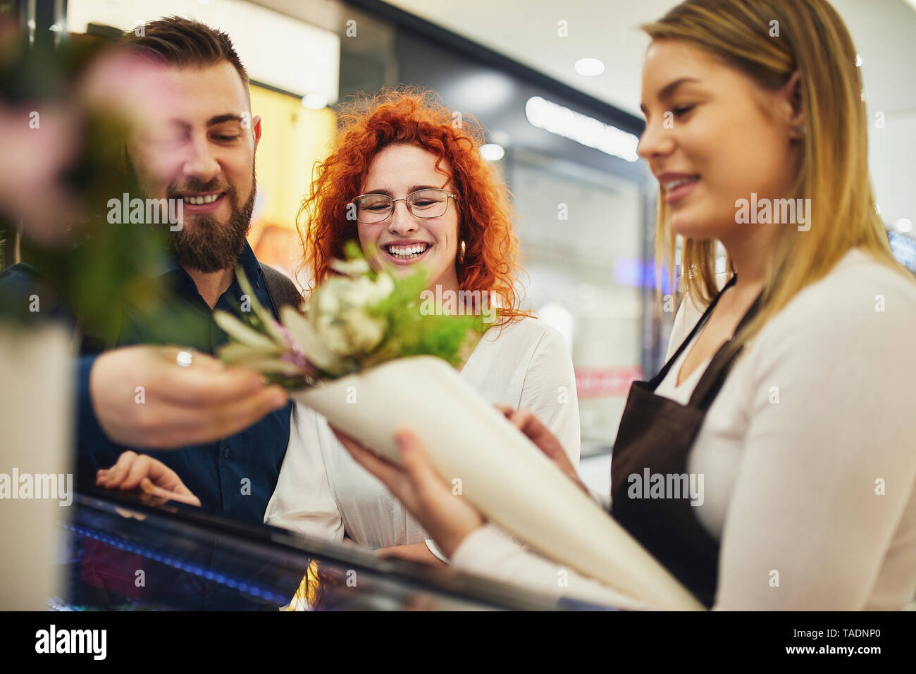 Florist wrapping flowers for couple in flower shop - Stock Image