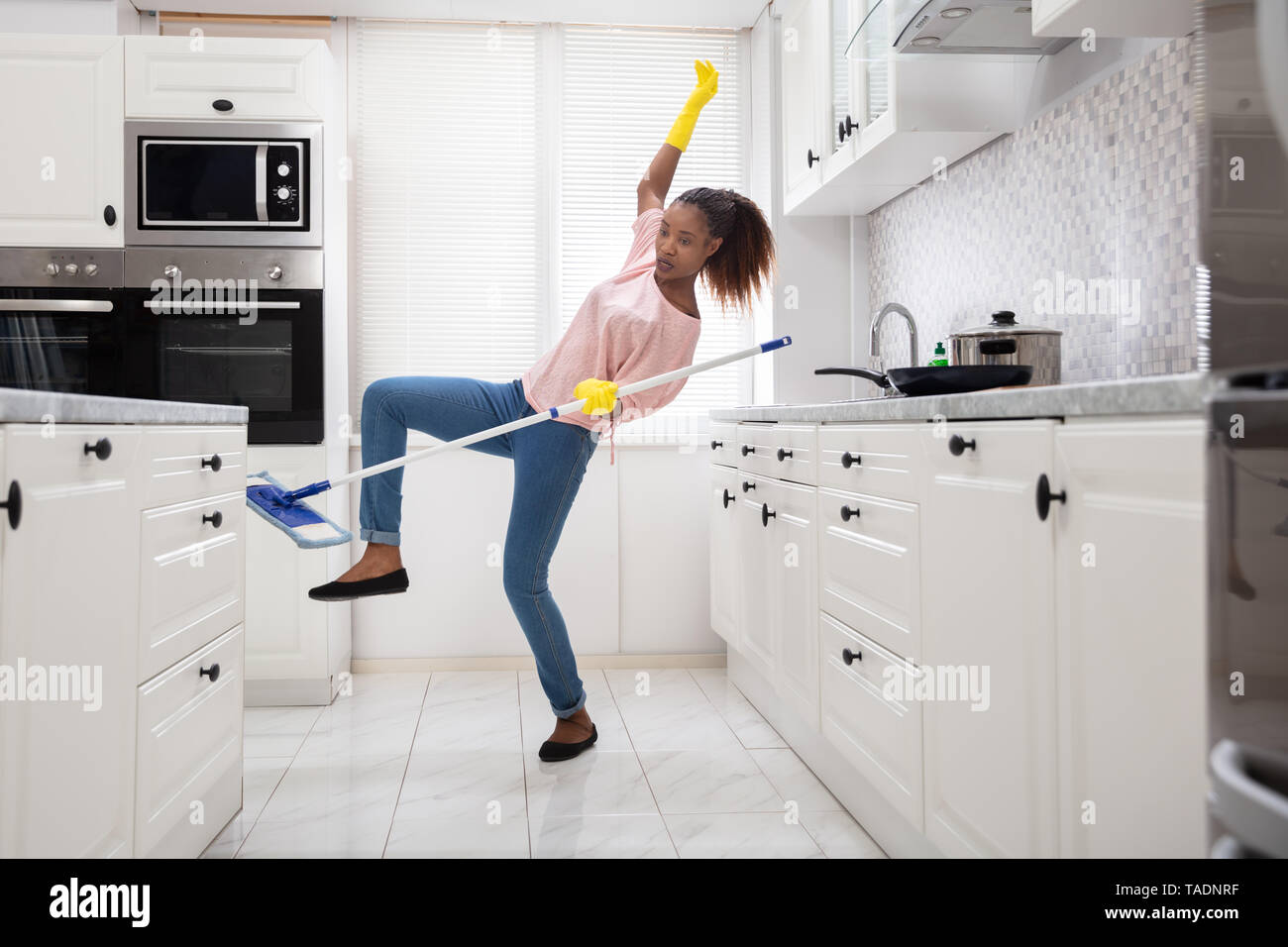 Close-up Of A Young African Woman Slipping While Mopping Floor In The Kitchen - Stock Image