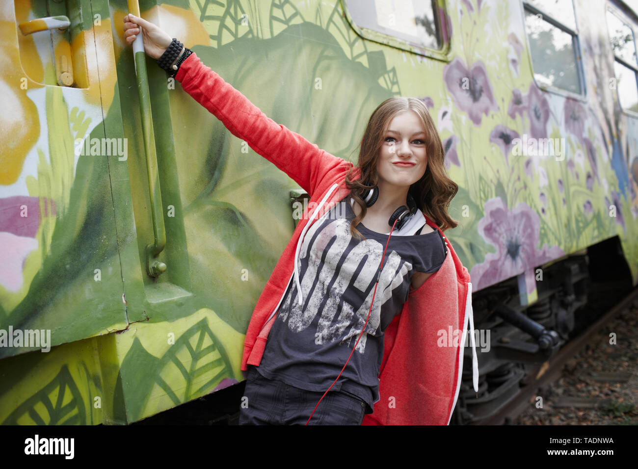 Portrait of teenage girl grimacing at a painted train car - Stock Image