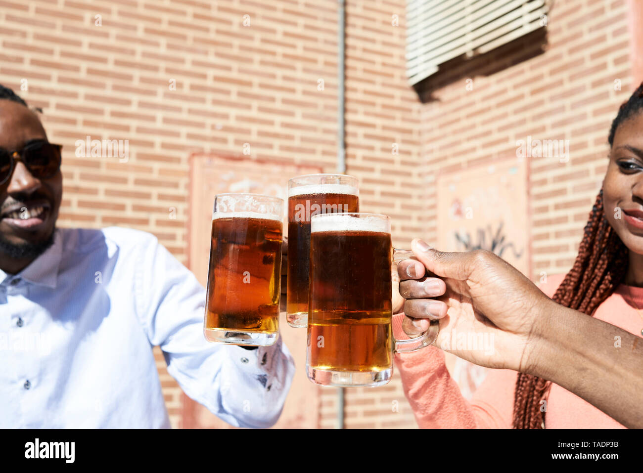Three happy friends drinking beer at an outdoor bar - Stock Image