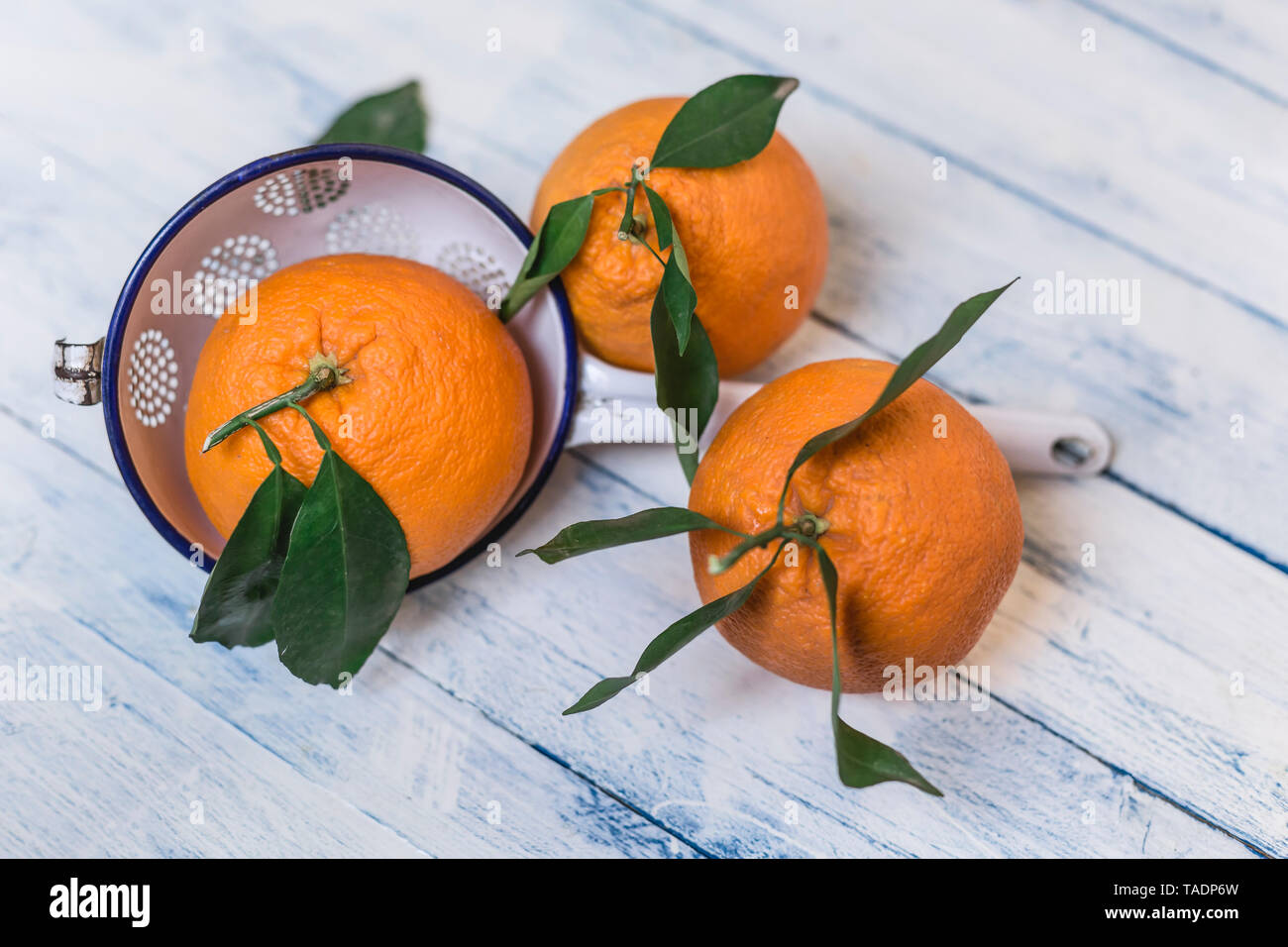 Three oranges with leaves and a colander on wood - Stock Image