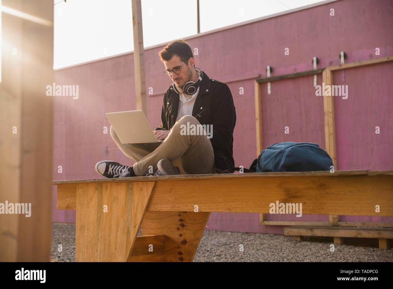 Young man sitting on platform using laptop - Stock Image