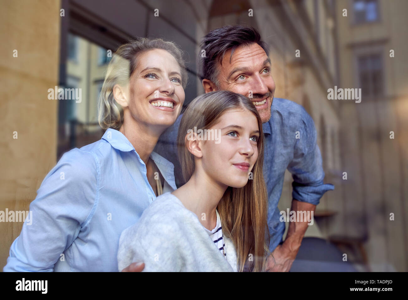 Portrait of happy family behind windowpane - Stock Image