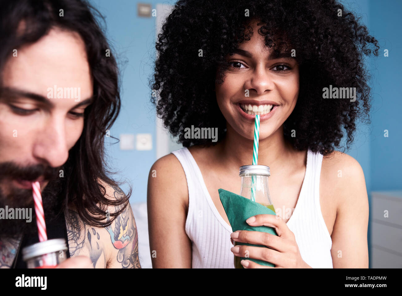 Portrait of smiling young woman with boyfriend drinking smoothie - Stock Image
