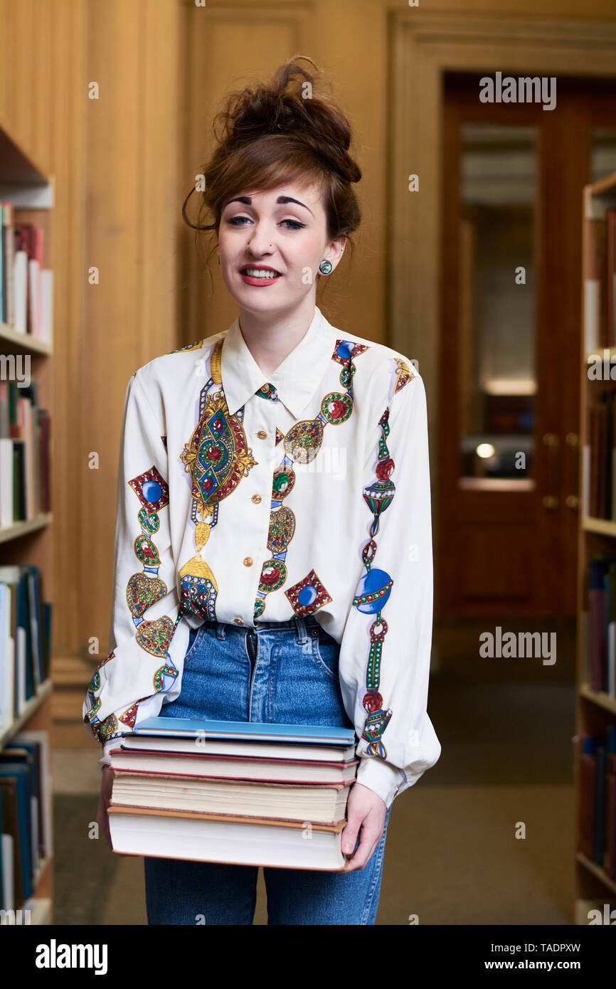 Female student with books in a public library - Stock Image
