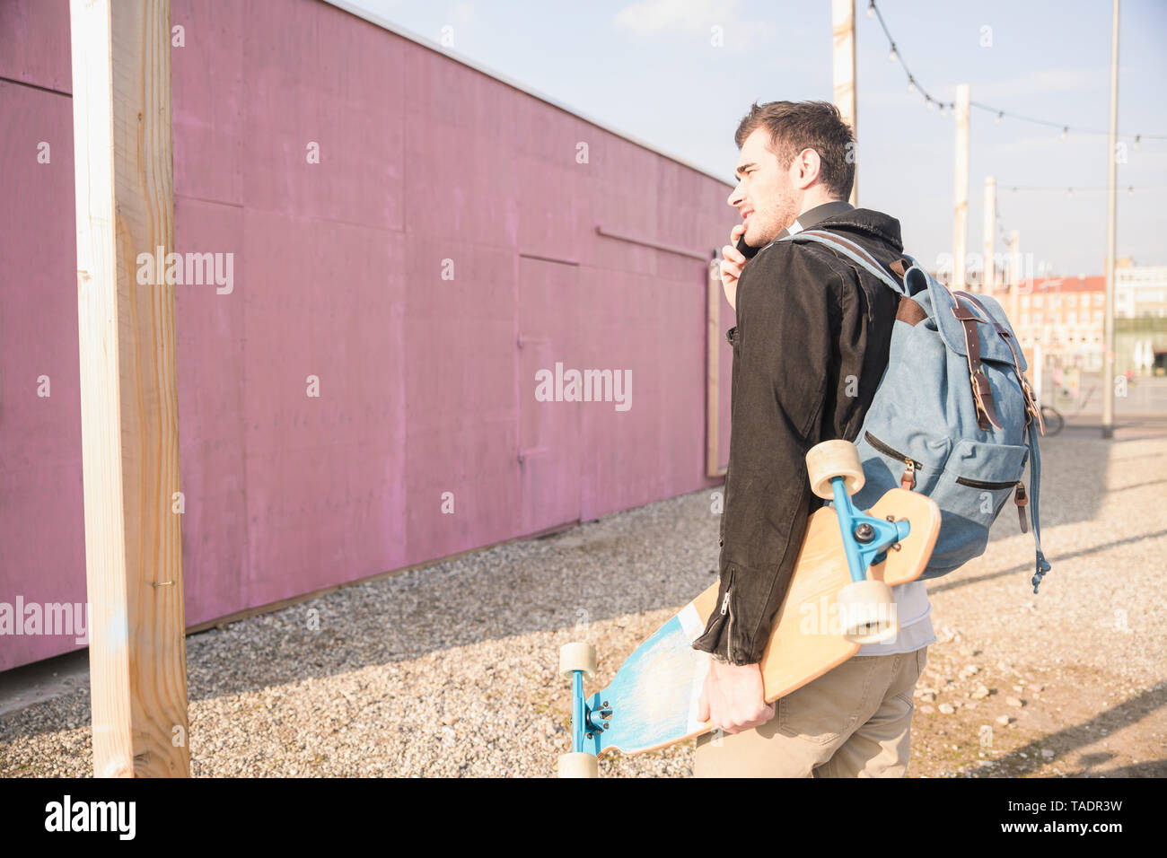 Young man with skatebaord and cell phone on the move in the city - Stock Image
