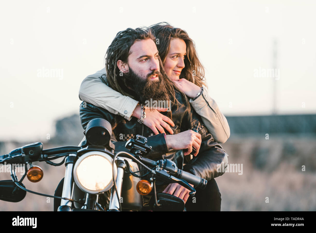 Portrait of couple on motorbike looking at distance - Stock Image