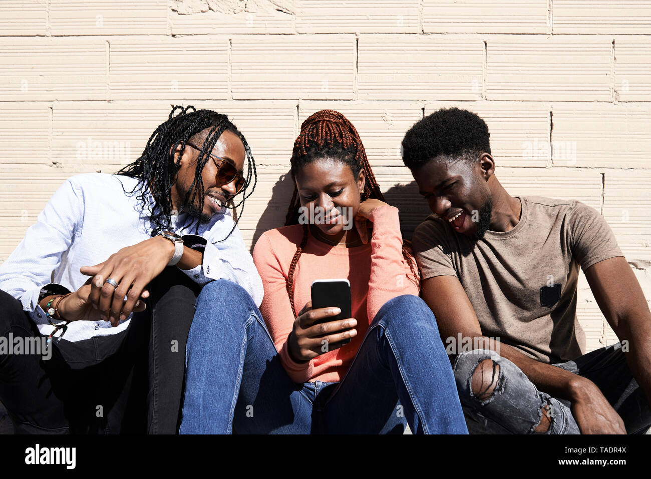 Three friends sitting together and watching a video on a smartphone outdoors - Stock Image