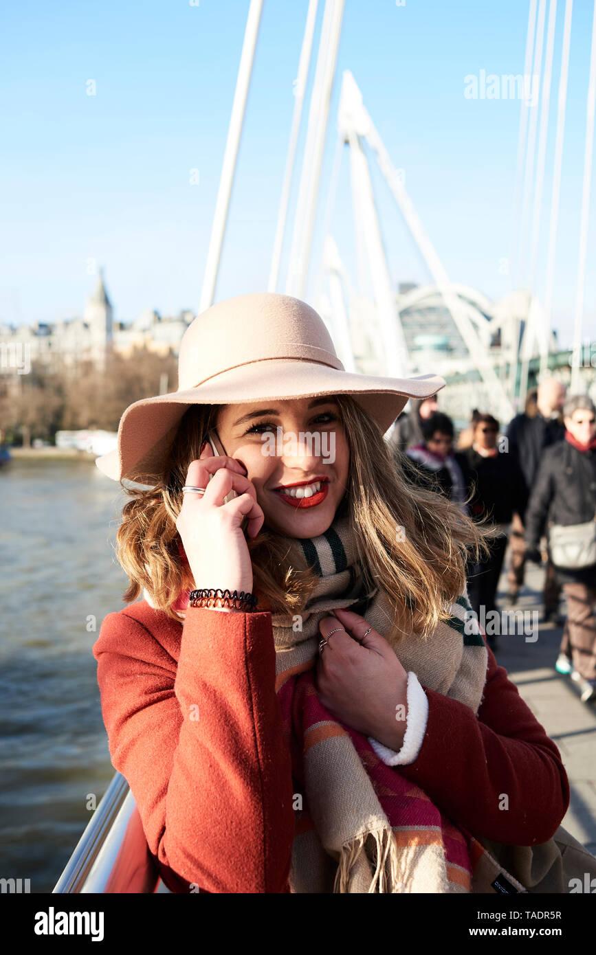 UK, London, stylish young woman talking on cell phone on Millennium Bridge Stock Photo