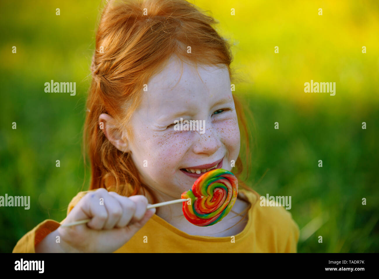 Portrait of happy girl eating a lollipop - Stock Image