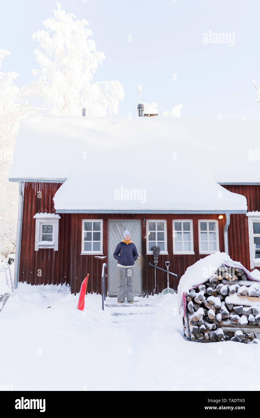 Finland, Kuopio, woman standing in front of farmhouse in winter Stock Photo