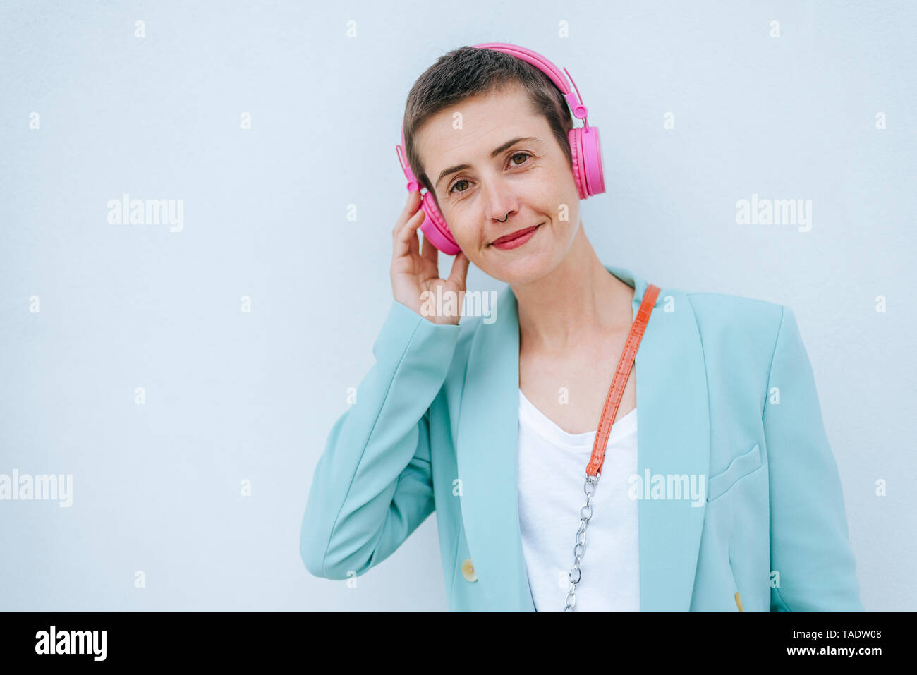 Woman dressed in jacket listening to music, pink headphones - Stock Image