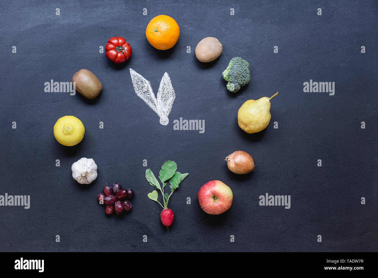 Fruits and vegetables buliding clock on dark ground with - Stock Image
