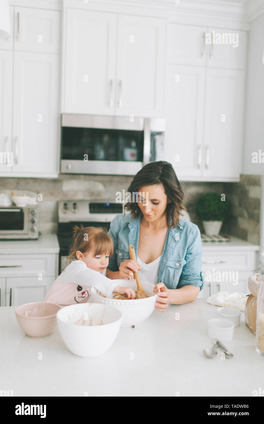 Mother and daughter making a cake together Stock Photo