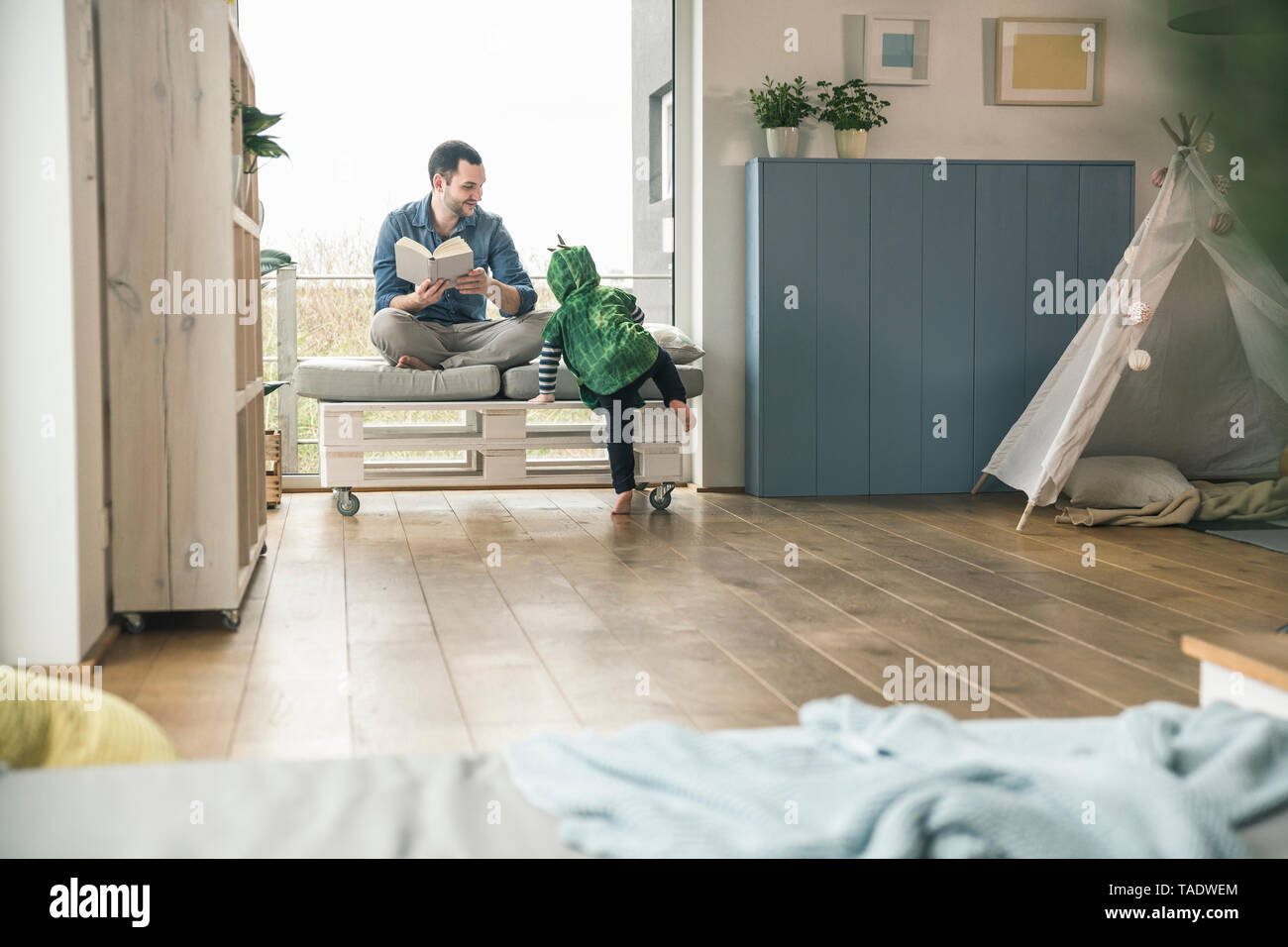 Boy in a costume and father reading book at home Stock Photo
