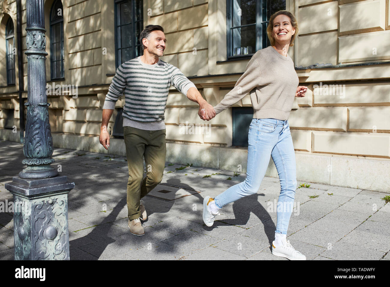 Happy couple running on pavement in the city - Stock Image