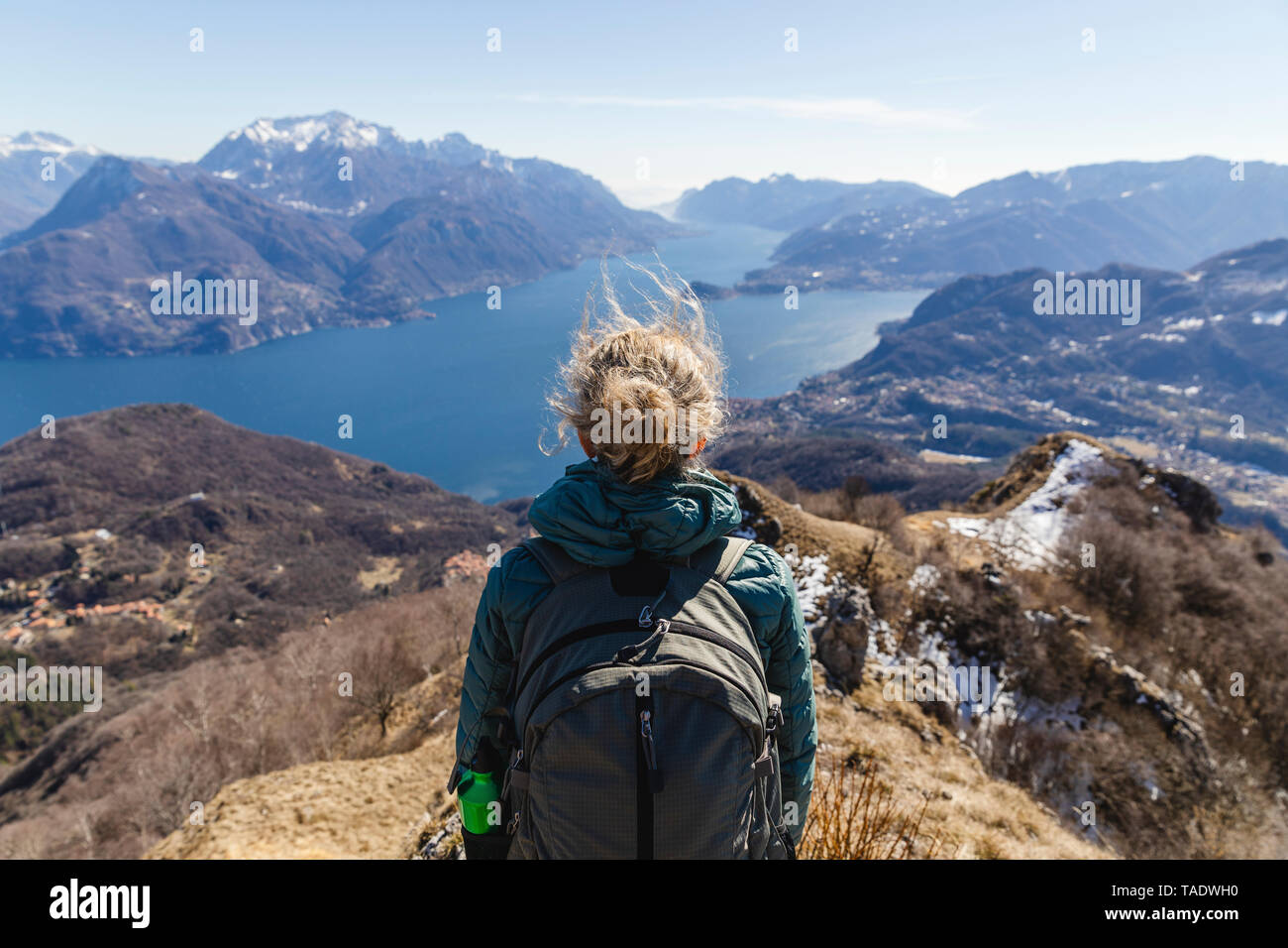 Italy, Como, Lecco, woman on a hiking trip in the mountains above Lake Como enjoying the view - Stock Image