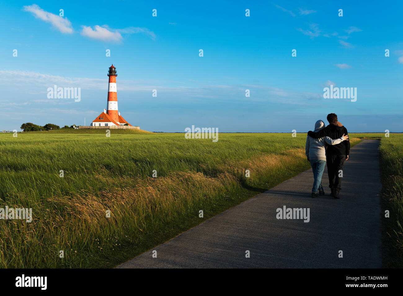 Germany, Westerhever, couple strolling along lighthouse - Stock Image