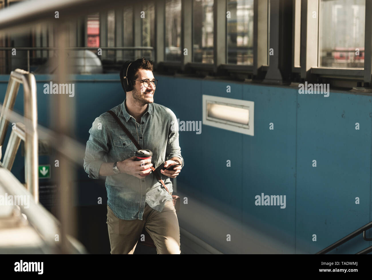 Smiling young man with headphones, cell phone and takeaway coffee walking at the station - Stock Image