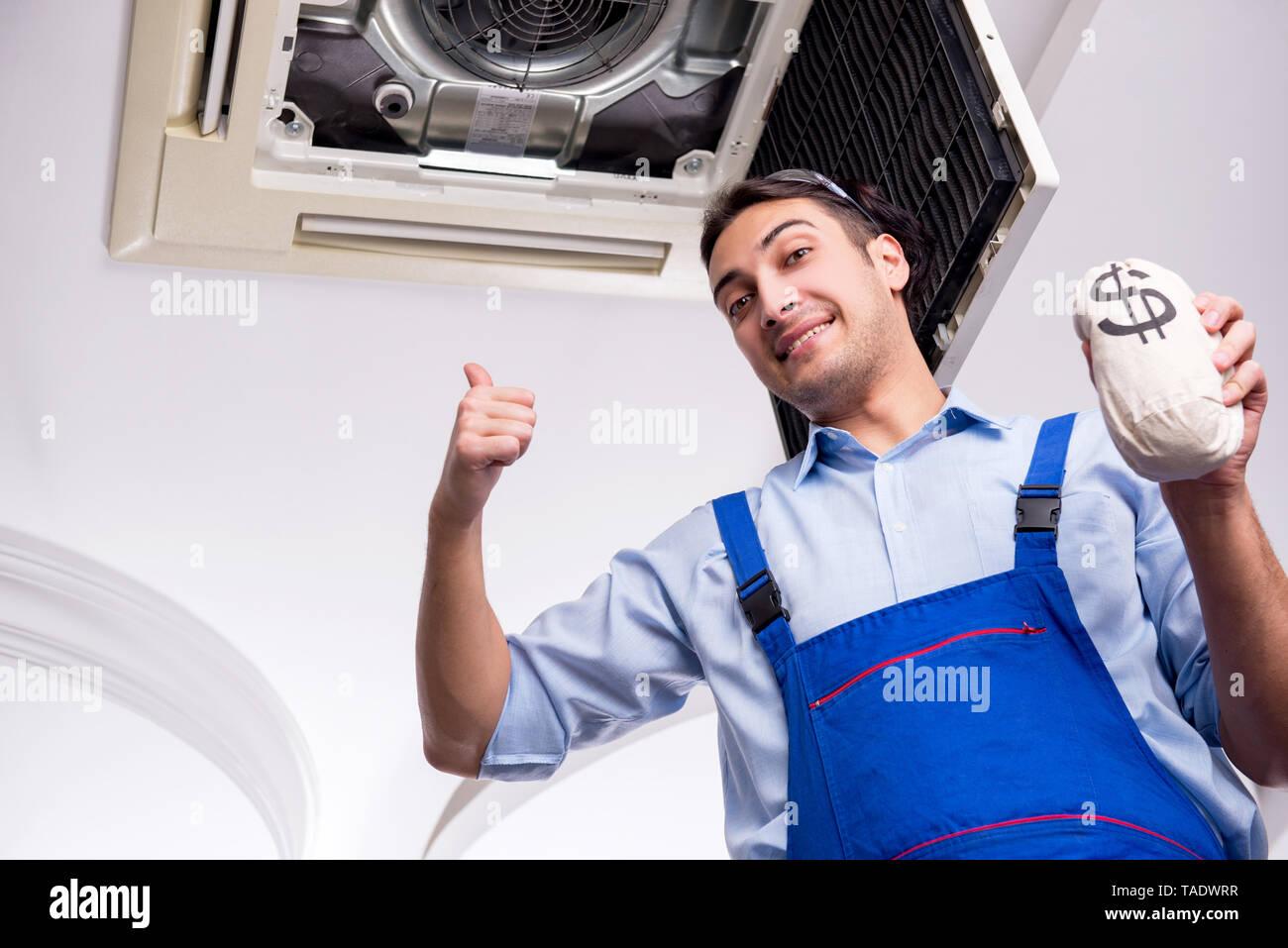 Young repairman repairing ceiling air conditioning unit - Stock Image