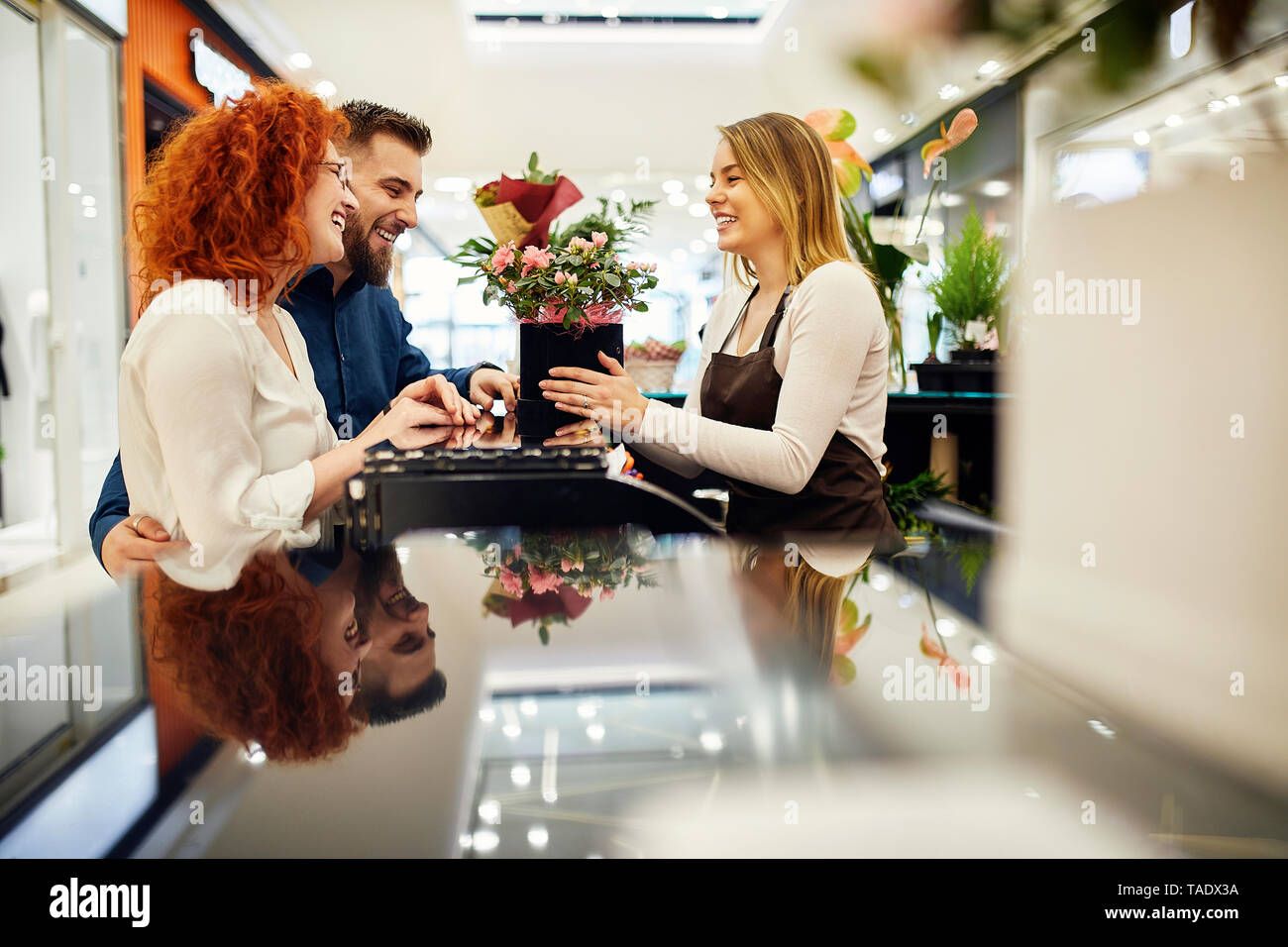 Happy couple and shop assistant with potted plant at counter in flower shop - Stock Image
