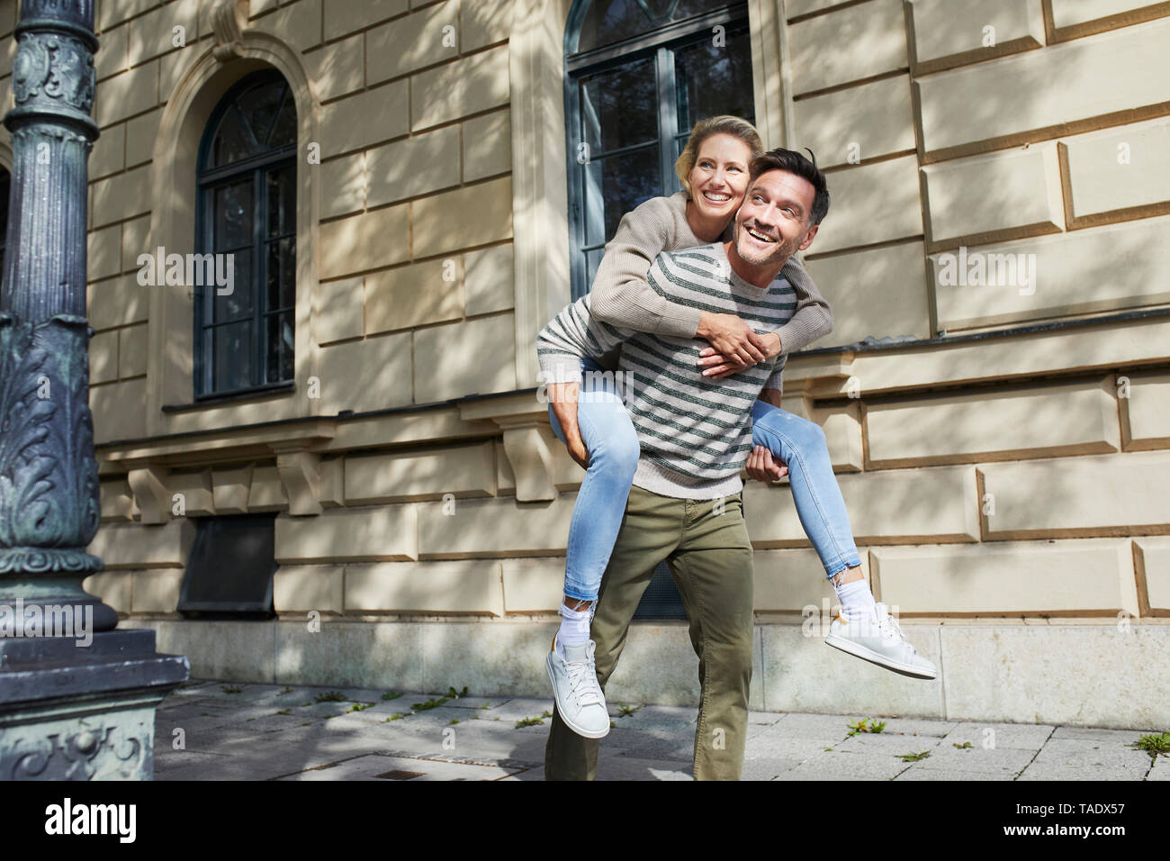 Happy man giving woman piggyback ride on pavement in the city - Stock Image