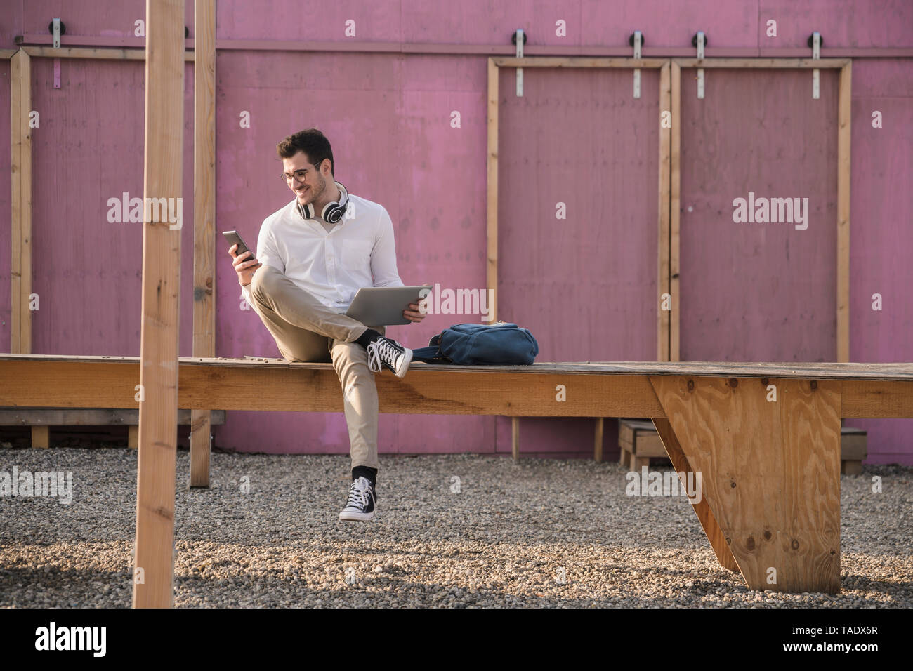 Smiling young man sitting on platform using cell phone - Stock Image