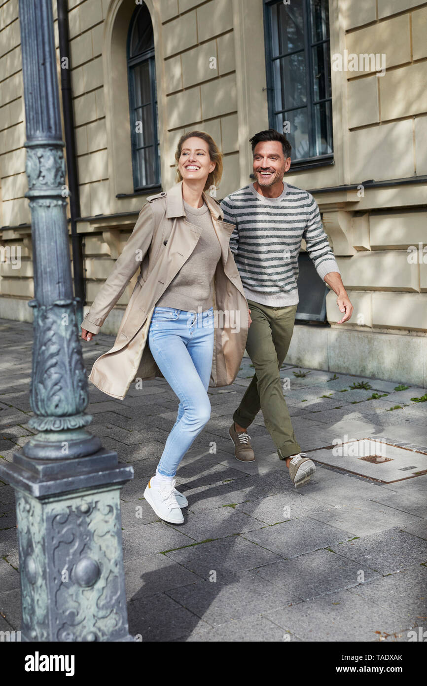 Happy couple walking on pavement in the city - Stock Image